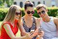 smiling friends with smartphones sitting in park - PhotoDune Item for Sale