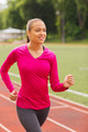 smiling young woman running on track outdoors - PhotoDune Item for Sale
