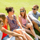 group of smiling friends outdoors sitting in park - PhotoDune Item for Sale