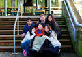Interracial family surrounding disabled boy in wheelchair outdoors by stairs - PhotoDune Item for Sale