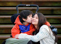 Disabled little boy kissing big sister on cheek - PhotoDune Item for Sale