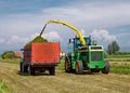 Harvester cutting field and loading into a Tractor Trailer - PhotoDune Item for Sale