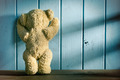 teddy bear stands in front of a blue wall - PhotoDune Item for Sale