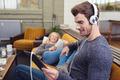 Man sitting listening to music on stereo earphones - PhotoDune Item for Sale