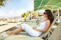 Woman Relaxing On Lounge Chair At Beach - PhotoDune Item for Sale