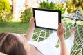 Woman Using Digital Tablet In Hammock At Park - PhotoDune Item for Sale