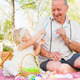 Loving Grandfather and Granddaughter Coloring Easter Eggs Together on Picnic Blanket At The Park. - PhotoDune Item for Sale