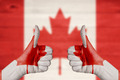 Canada flag painted on female hands thumbs up - PhotoDune Item for Sale