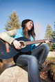 Sitting on a rock playing guitar. - PhotoDune Item for Sale
