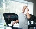 Tired senior man on a treadmill with towel and bottle of water
