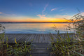 Blue and Orange Sunset over Boardwalk on the shore of a Lake - PhotoDune Item for Sale