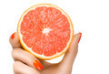 Female Hand Holding a Luscious Healthy Grapefruit. Isolated - PhotoDune Item for Sale