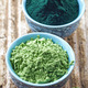 bowl of spirulina algae powder and wheat sprout powder on wooden - PhotoDune Item for Sale