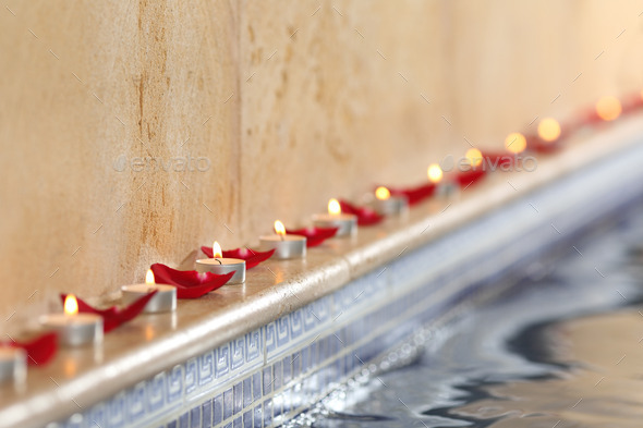 Candles and rose petals in a spa pool relax concept