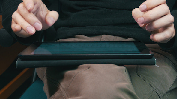 Male Hands Typing on a Tablet Computer