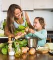 Woman with baby cooking at kitchen - PhotoDune Item for Sale