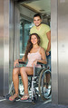 man helping handicapped girl at elevator - PhotoDune Item for Sale