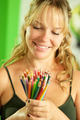 Young female artist looking at colored pencils and smiling - PhotoDune Item for Sale