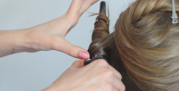 Hairdresser Twists Hair With a Curling Iron