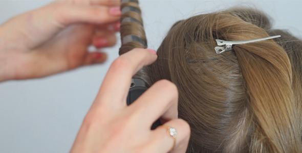 Stylist Hairdresser Makes Hairdress Using Curling