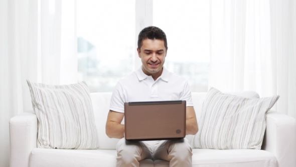 Man Working With Laptop Computer At Home