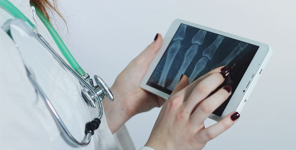 Female Doctor Examines an X-ray with a Tablet