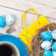 Easter background with blue and white eggs in nest, yellow tulip - PhotoDune Item for Sale