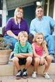 Portrait Of Family Sitting Outside House