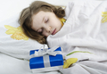 Little girl sleeping in bed with gift - PhotoDune Item for Sale