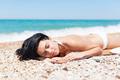 woman sleeping on beach sunbathing tanning