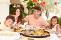 Hispanic Family Enjoying Outdoor Meal At Home Together