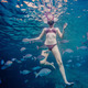 Girl Snorkeling and Surrounded with Chopa Fish - PhotoDune Item for Sale