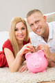 Couple Inserting Coin In Piggybank - PhotoDune Item for Sale