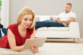 Woman Using Digital Tablet With A Man On Sofa - PhotoDune Item for Sale