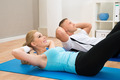 Young Couple Doing Crunches - PhotoDune Item for Sale