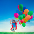 Superhero with toy balloons in spring field - PhotoDune Item for Sale