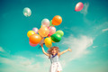 Child jumping with toy balloons in spring field - PhotoDune Item for Sale