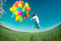 Woman jumping with toy balloons in spring field - PhotoDune Item for Sale