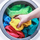 hand and puts the laundry into the washing machine - PhotoDune Item for Sale