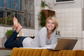 Smiling pretty woman relaxing with her laptop - PhotoDune Item for Sale