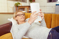Woman with Eyeglasses Lying on a Sofa with a Book - PhotoDune Item for Sale
