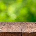 Empty wooden table against green background - PhotoDune Item for Sale