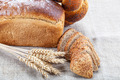 Rye bread, wheat loaf with poppy seeds and ears on sacking. - PhotoDune Item for Sale