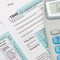 US 1040 Tax Form and calculator over it - PhotoDune Item for Sale