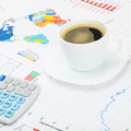 Coffee cup and calculator over financial charts - studio shot - PhotoDune Item for Sale