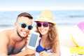 Happy couple showing smartphone at the beach - PhotoDune Item for Sale