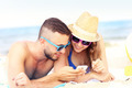 Couple using smartphone at the beach - PhotoDune Item for Sale