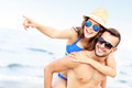 Young couple pointing at something at the beach - PhotoDune Item for Sale