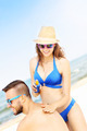 Woman applying sunscreen on the back of her man - PhotoDune Item for Sale
