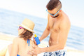 Man applying sunscreen on the back of his woman - PhotoDune Item for Sale